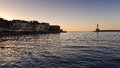 Panoramic view of the entrance to Chania harbor with lighthouse at sunset, Crete Royalty Free Stock Image