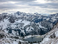 Panoramic view of the snow-capped Alps and the mountain lake. Royalty Free Stock Photo