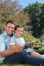 Papa et fils avec le pc de comprimé souriant dans l appareil photo Image stock