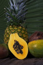 Papaya half mangos pineapple of a ripe with coconut and palm frond in background Royalty Free Stock Photography
