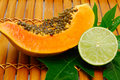 Papaya and lime on bamboo Royalty Free Stock Images