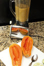 Papaya seeds blended decades old chrome black white blender with in glass container and two halves of a long on a cutting Royalty Free Stock Image