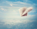 Paper airplane flying in the sky Stock Photos