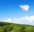 Paper airplane flying in the sky over forest Royalty Free Stock Image