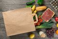 Paper bag full of different groceries on wooden background Royalty Free Stock Photo
