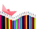 Paper boat on an array of color pencils a floating a row isolated white with copy space Stock Photography