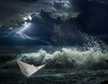 Paper boat in ocean storm with lgihting and waves Royalty Free Stock Photo