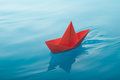 Paper boat sailing red on water causing waves and ripples Royalty Free Stock Image