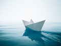 Paper boat sailing on water causing waves and ripples Stock Photo