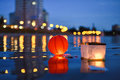 Paper Chinese lanterns floating in river with city lights reflec Royalty Free Stock Photo