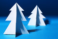 Paper christmas trees over blue background Stock Photo