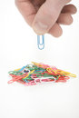Paper clip in hand holding across others clips Royalty Free Stock Photo