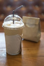 Paper cup of iced coffee on wooden table Royalty Free Stock Photo