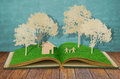 Paper cut of family symbol on old grass book. Royalty Free Stock Photos