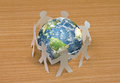 Paper cut of people standing in a circle around globe Royalty Free Stock Photo