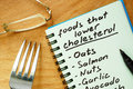 Paper with foods that lower cholesterol list on a wooden board Stock Photo