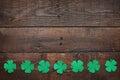 Paper green clover shamrock leaf border on dark wooden background Royalty Free Stock Photo