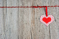 Paper heart hanging on clothesline on old wooden background Royalty Free Stock Photos