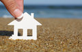Paper house on the beach. Concept of mortgage Royalty Free Stock Photo