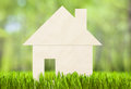 Paper house on green grass mortgage concept Stock Image