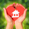 Paper house and heart in female hands over nature green sunny background concept Stock Image