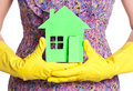 Paper house on woman hands in gloves concept Stock Photos