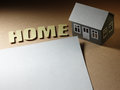 Paper houses house sheet and the word home on the cardboard surface Royalty Free Stock Images