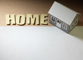 Paper houses house sheet and the word home on the cardboard surface Royalty Free Stock Photo