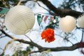 Paper lanterns chinese and pom pom decorations in outdoor party setting flying in the wind Royalty Free Stock Image