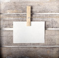 Paper note with a pinch on wooden background Royalty Free Stock Image