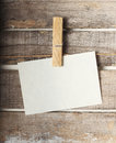 Paper note with a pinch on wooden background Royalty Free Stock Photo