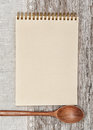 Paper notebook wooden spoon and linen fabric on the old wood background Stock Photo