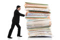 Paper pusher stock image of businessman pushing a giant stack of documents isolated on white background Stock Photo