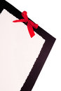 Paper with red bow blank white stationary on a piece of black cardboard a all on an isolated white background Stock Images