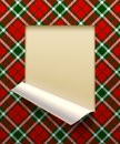 Paper sheet cut framed and partially rolled up with tartan backg Royalty Free Stock Photo
