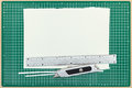 Paper sheet with metal ruler and utility knife on green cutting Royalty Free Stock Photo