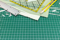 Paper sheets with metal ruler and utility knife on green cutting Royalty Free Stock Photo