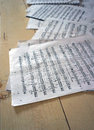 Paper sheets with musical notation few papers staff score and notes on a wooden floor Stock Photo