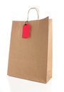 Paper shopping bag with handles and empty red label Royalty Free Stock Images