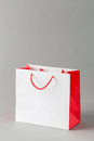 Paper shopping bag white and red color isolated on gray background Stock Photos
