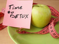 Paper with time to detox, apple and measuring tape.