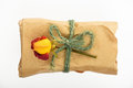 Paper wrapped gift with jute bow and rose on white Royalty Free Stock Photo