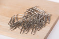 Paperclips on wooden and white background Royalty Free Stock Photography