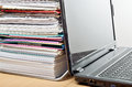 Paperwork a huge pile of on a desk beside a laptop computer Royalty Free Stock Photo