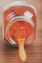 Paprika spice in glass jar with wooden spoon Royalty Free Stock Photo