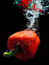 Paprika in water plunged into with air bubbles ascending Stock Image