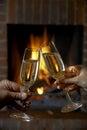 Par med exponeringsglas av champagne relaxing by fire Arkivfoton