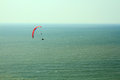 Para glider flying in blue sky over the ocean red Stock Photos