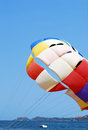 Parachute and sea landing over blue sky Stock Photos