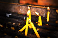 Paraffin taper yellow candles burning on the altar Stock Photos